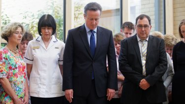 Britain's Prime Minister, David Cameron, centre, stands in silence during a visit to Chipping Norton Health Centre in his constituency in Witney, England.