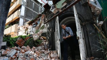A man walks out of the door frame of a building that collapsed after the earthquake.