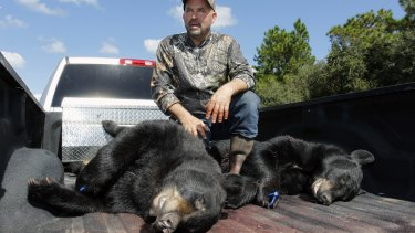 Richard Sajko, of Valrico, Florida, explains how he killed one of the two bears on the back of his pick-up truck at the Rock Springs Run Wildlife Management Area near Lake Mary on Saturday.