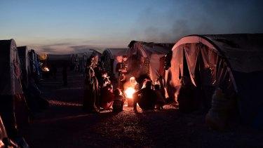 Syrian Kurdish refugees gather around fire in a refugee camp in Suru.