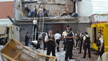 Guards and police inspect the building blown up by the armed gang in the early morning in Ciudad del Este in Paraguay on Tuesday.