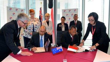 DFAT secretary Peter Varghese (left) signs a Memorandum of Understanding with Indonesian Head of Counter-Terrorism Saut Usman as Indonesian and Australian ministers look on during the third Australia-Indonesia 2+2 meeting on Monday.