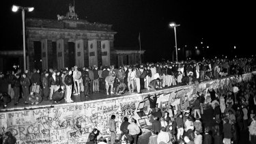 East and West German citizens celebrate as they climb the Berlin wall at the Brandenburg Gate on November 9, 1989.