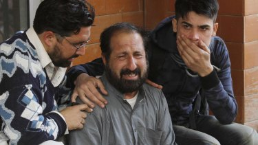 Relatives of a student, who was injured during an attack by Taliban gunmen on the Army Public School, comfort each other outside Lady Reading Hospital in Peshawar.