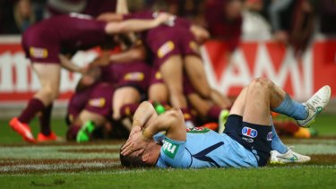 Dismal: Josh Morris slumps to the ground as Queensland cross for yet another try in the Origin decider.