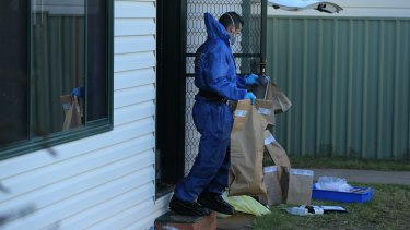 A NSW Forensic officer carries evidence bags into the backyard of Vincent Stanford's home.