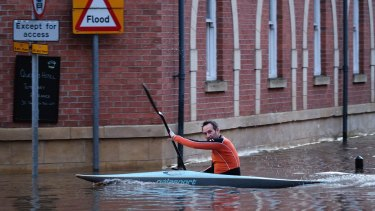 A man paddles his kayak along a flooded street  in York on Sunday.