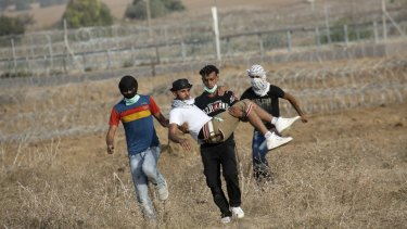 Palestinian protesters evacuate a wounded youth during clashes with Israeli soldiers by the Israeli border with Gaza last month.