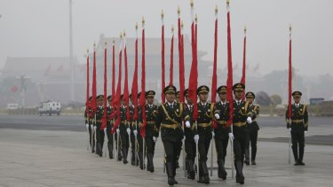 An honour guard in Tiananmen Square in Beijing last year, standing to attention as smog swirls in the background.