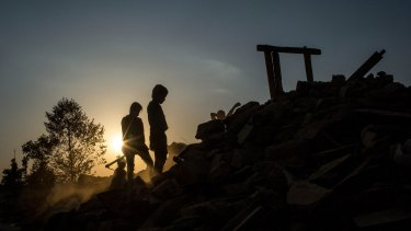 People sort through the rubble of their home looking for any salvageable item in Jalkini, Nepal, on Tuesday.