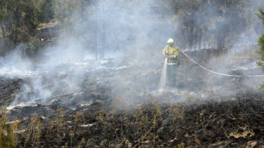 Fire fighters from ACT Fire and Rescue, ACT Rural Fire Service and from TAMS control a grass fire near Jim Pike Avenue in Gordon in November 2014.