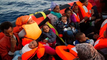 Migrants from Eritrea hold their children after being rescued from a crowded wooden boat fleeing Libya.