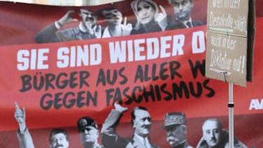 Anti-fascist demonstrators hold up a banner declaring 'They're back!'  showing photos of  dictators and fascists from the 20th century alongside some of the European leaders attending the meeting in Koblenz.