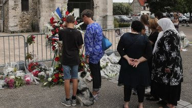 Residents pay tribute at a makeshift memorial in front of the Saint Etienne church where Priest Jacques Hamel was killed on 26 July.