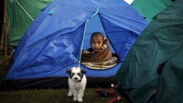 A boy sits inside a tent in Kathmandu.