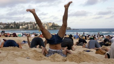 Denial: Australians burying their heads in the sands of Bondi Beach to send a message to Prime Minister Tony Abbott about the dangers of climate change.