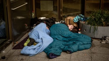A couple sleep through the mid-morning on the corner of Collins and King Streets.