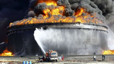 Firefighters try to put out a blaze in a storage tank at the key Libyan port of Sidra last week.