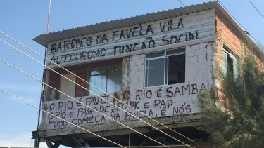 """One original house was allowed to remain at Vila Autodromo. The graffiti states: """"Social purpose hut of Vila Autodromo favela"""" and """"Rio is favela, Rio is samba, Rio is pagode, funk and rap. Everything starts in favelas. It is us""""."""