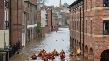 Members of the Mountain Rescue team wade through floodwater in Skeldergate, York, on Monday.