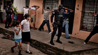 School children walk by as heavily armed members of a police anti-gang force search men in El Salvador.