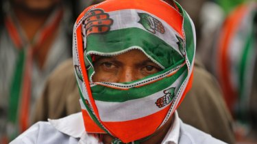 A supporter of India's main opposition Congress party covers himself with party's scarf during an election rally at Dhrangadhra in Gujarat.