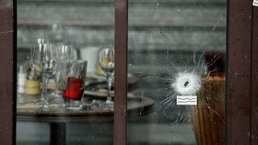 Bullets holes are seen through the glass door of a cafe near Casa Nostra.