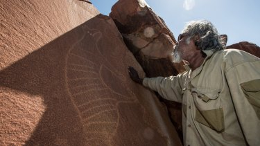 Senior cultural ranger at Murujuga National Park, Jakari Togo, stands next to a rock carving of a thylacine on the Burrup Peninsula, Western Australia.