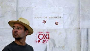 """A man walks past the Athens headquarters of Bank of Greece where graffiti and stickers reading """"No"""" can be seen."""