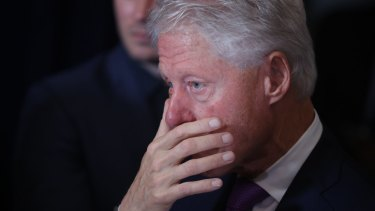 Bill Clinton listens as his wife Hillary Clinton delivers her concession speech in New York.