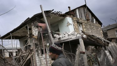 An ethnic Armenian man walks past a destroyed house during the fighting in Martakert province in the separatist region of Nagorno-Karabakh on Monday.