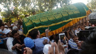 People carry the coffin of  Ko Ni to his final resting place.