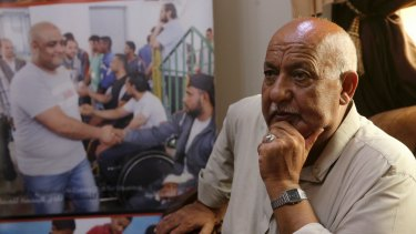 Khalil al-Halabi, 63, the father of Mohammed al-Halabi,  beside a picture of his son at the family home in Gaza City.