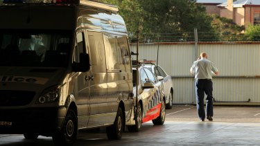 A police officer speaks on the phone at Maitland Police Station on Tuesday, where a woman was found dead.