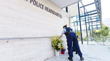A police officer lays flowers at in tribute to Curtis Cheng, who worked for the police finance department.