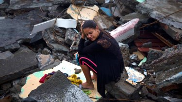 A woman cries amid the rubble of her home, destroyed by Hurricane Matthew in Baracoa, Cuba.