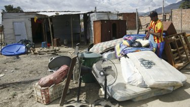 A man stands near houses used by people who do not possess proper documentation in Venezuela.