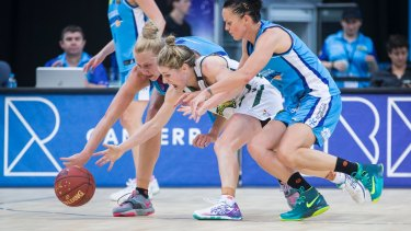 Sport. January 4th 2015.  Women's National Basketball League round 11, Canberra Capitals v Dandenong Rangers at the AIS Arena, Canberra.  From left Abby Bishop of the Canberra Capitals, Kathleen MacLeod of the Dandenong Rangers and Kirsten Veal of the Canberra Capitals vie for a way ball.  Canberra Times photo by Matt Bedford