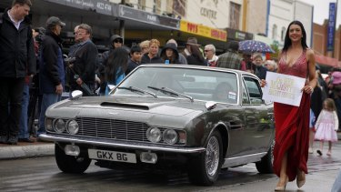 Serena Greaves walks alongside the original Aston Martin DBS from On Her Majesty's Secret Service, driven by owner Sigi Zidziunas during the SpyFest Street Parade on Saturday.