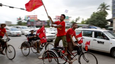 Members of Myanmar opposition leader Aung San Suu Kyi's National League for Democracy party rally on trishaws through a suburb in Yangon, Myanmar on Tuesday.