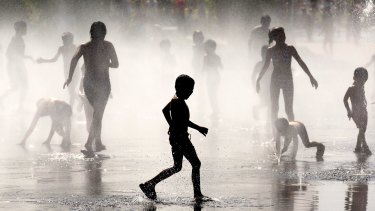 Children cool off under a fountain in Madrid in July this year.