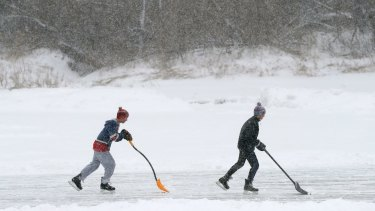 Pond hockey players attempt to shovel snow faster than it can fall in Yarmouth, Maine.