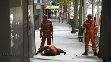 Police and SES search for a mobile phone along Collins Street on Friday.
