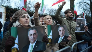 Supporters of Reza Pahlavi, the heir to Iran's deposed monarchy, carry his image during protests outside the Iranian embassy in London this week.