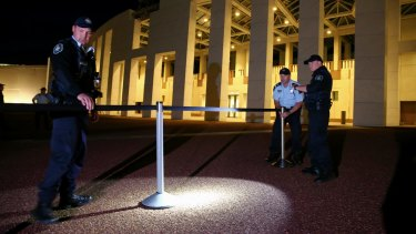 AFP officers set up bollards to cordon off the media on the forecourt of Parliament House.