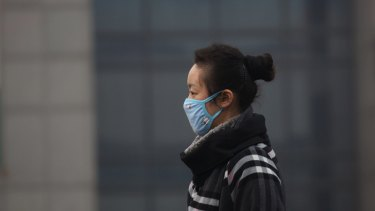 A woman wears a mask as she walks on a street in Beijing.