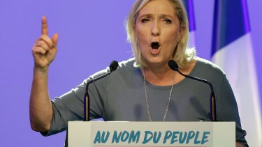 """France's far-right National Front leader Marine Le Pen speaks behind the slogan """"In the name of the people""""."""