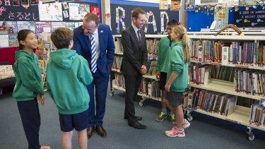 Andrew Barr, left, and Shane Rattenbury meet students at Kaleen Primary on Monday, where they announced plans to phase out paper forms and notes in schools.