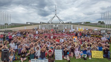 Protesters at Parliament House in Canberra cross their arms in solidarity with the Manus Island detainees.