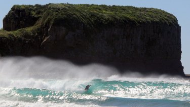 A surfer battles the waves at Bombo Beach.